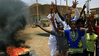 Sudanese protesters gesture and chant slogans at a barricade along a street, demanding that the country's Transitional Military Council hand over power to civilians, in Khartoum, Sudan on 5 June 2019
