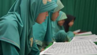 Siswi membaca Quran pada bulan Ramadan.