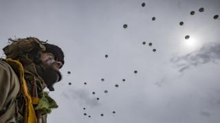 Parachutist watches others drop to the ground