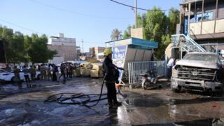 A firefighter hoses down a street after the suicide bomb attack