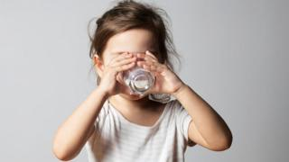 طفلة تتناول كوبا من الحليب