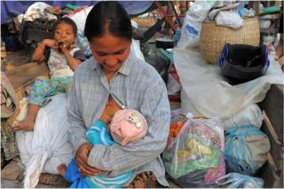 A Cambodian villager feeds her baby in a camp after fleeing from their home near the Preah Vhear temple in Preah Vihear province, some 500 kilometers northwest of Phnom Penh on 8 February 2011