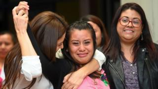 Evelyn Hernández chora e é amparada por outras mulheres sorrindo dentro de sala