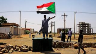 A Sudanese protester holds a national flag as he stands on a barricade along a street, demanding that the country
