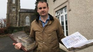 Rev Alastair Donaldson holding the church register books