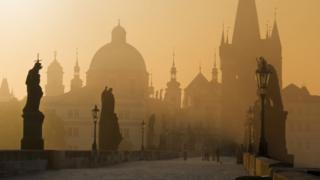 Prague's famous Charles Bridge is seen in an early morning mist, lending the scene a mysterious ambience