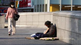 A woman wears a face mask as she walks past a homeless man in Osaka, Japan