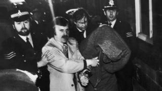 El arresto de Peter Sutcliffe (oculto bajo una manta)