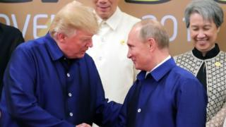 US President Donald Trump (L) shakes hands with Russia's President Vladimir Putin (R) as they pose for a group photo at Apec summit on 10 November