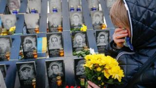 Жінка біля пам'ятних дошок загиблих на Майдані