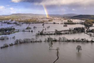 A rainbow appears over flooded fields in the Wye Valley, near the hamlet of Wellesley.