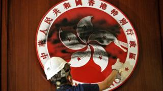 A protester defaces the Hong Kong emblem with black paint