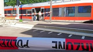 Policemen stand by a train at the station in Salez.