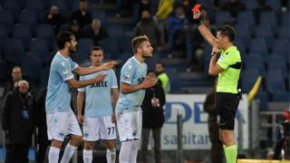 "Piero Giacomelli presents a red card to Lazio""s Italian midfielder Ciro Immobile"