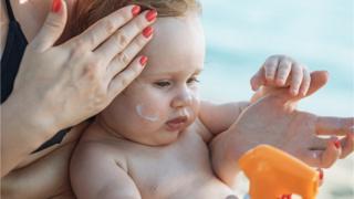 Mum applying sunscreen to baby