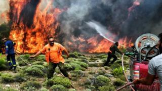 Imagem mostra quatro homens tentando controlar as chamas na maior onda de incêndios na Crécia em mais de uma década