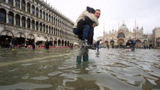 A man carrying a woman on his shoulders walks in high water at San Marco Square in Venice, northern Italy, 1 November 2018.