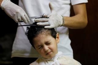 A boy grimaces as his hair is clasped and trimmed by a gloved barber.