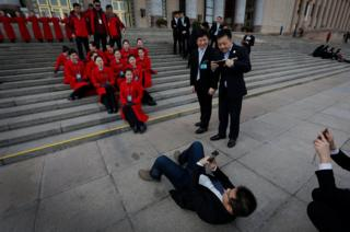 A worker takes picture of a journalist on the steps of the Great Hall of the People in Beijing, China