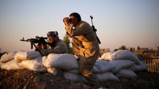 Kurdish Peshmerga fighters observe the front line with Islamic State, in Gwar, northern Iraq September 23, 2014.