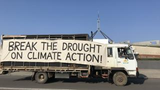 A lorry drives past parliament with a big sign on the side which reads: 'Break the drought on climate action!'