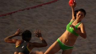 Shen Ping of China is seen shooting a ball during the Women's Handball Final at the 2nd Asian Beach Games in Muscat. The player is sporting a green bikini.