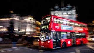 Bus tingkat di London melaju di malam hari.