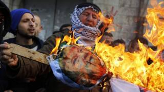 Palestinian protesters burn an effigy of Donald Trump in Nablus, West Bank, on 7 December 2017