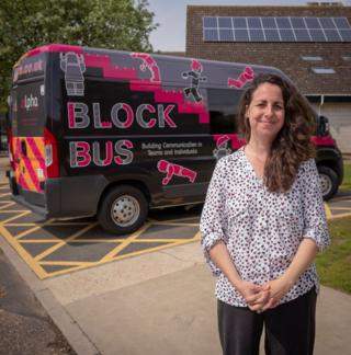 Founder Amy Eleftheriades stands in front of the Alpha Bus