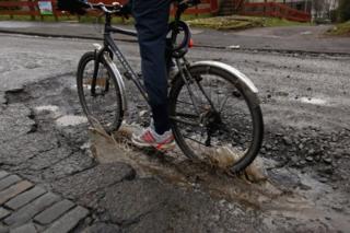 Cyclist going through pothole
