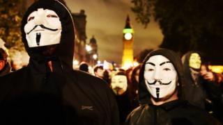 Anti-capitalist protesters wear Guy Fawkes mask during march organised by the group Anonymous