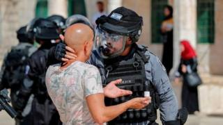 رجل شرطة إسرائيلية ممسكا بشاب فلسطيني