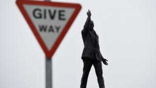 The statue of Edward Carson at Stormont next to a 'Give Way' road sign