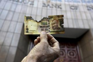 In this Nov. 16, 2016 file photo, a man holds a charred facsimile of the discontinued Indian currency 500 note after a protest by a traders association demanding adequate arrangement to exchange discontinued currency notes outside Reserve Bank of India in Kolkata, India.