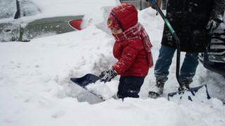A two year old boy helps his dad shovel snow in Washington DC in America.