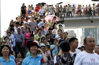 People watch military helicopters on a pedestrian overpass outside the closed area during the military parade to mark the 70th anniversary of the end of World War Two, in Beijing, China, 3 September 2015