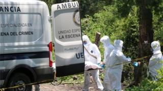 Forensic technicians carry a body from the pickup truck Michoacan July 30, 2016