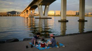 A family picnics by the banks of the Han River in Seoul