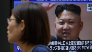 """A pedestrian walks past a TV screen on a street displaying North Korean leader Kim Jong-un after North Korea""""s missile launch, in Tokyo, Japan, 29 August 2017"""