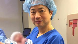Джон Чжан с младенцем на руках