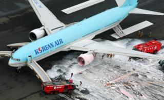 An aerial picture showing a Korean Air with fire trucks spraying foam at an engine, at Haneda airport in Tokyo 27 May 2016