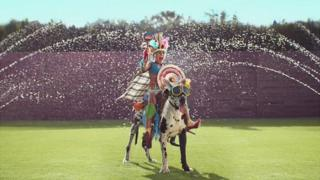 Still from advert showing boy riding dog through sprinklers