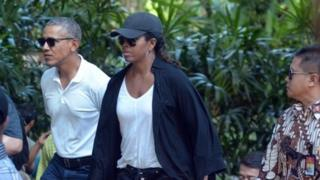 Former US President Barack Obama and his wife Michelle walk during a visit to Tirta Empul Temple in Gianyar, Bali (27 June 2017)