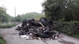 , Tyres fly-tipped in road near Minnie Pit memorial