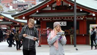 Tourists looking at a guide book in at Sensoji temple at Tokyo