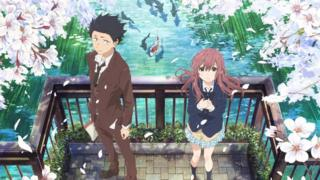 A still image shows two teenagers standing on a bridge over a koi pond, with the girl looking hopefully upward, while the boy is turned slightly away