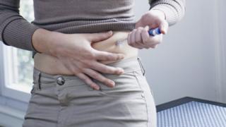 Woman having insulin injection