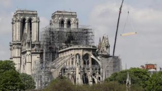 Fire fighters are at work on top of a tower of Notre-Dame Cathedral, as a crane lifts up constreuction material in Paris on April 17, 2019,
