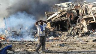 A Somali man reacts next to a dead body on the site where a car bomb exploded at the center of Mogadishu, on October 14, 2017