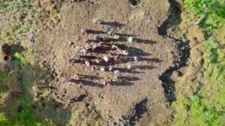 Visão aérea de um grupo de pessoas sobre um monte de pedra com bordas irregulares em meio à vegetação de savana